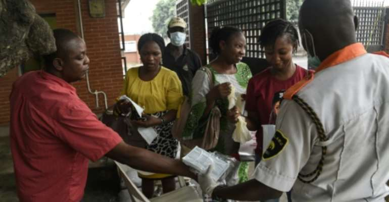 Visitors to a state hospital in Lagos collect facemasks and gloves and have their hands sanitised.  By PIUS UTOMI EKPEI (AFP)