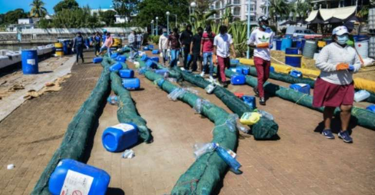 Volunteers make oil barriers to absorb leaked oil from the ship.  By Sumeet MUDHOO (L'Express Maurice/AFP/File)