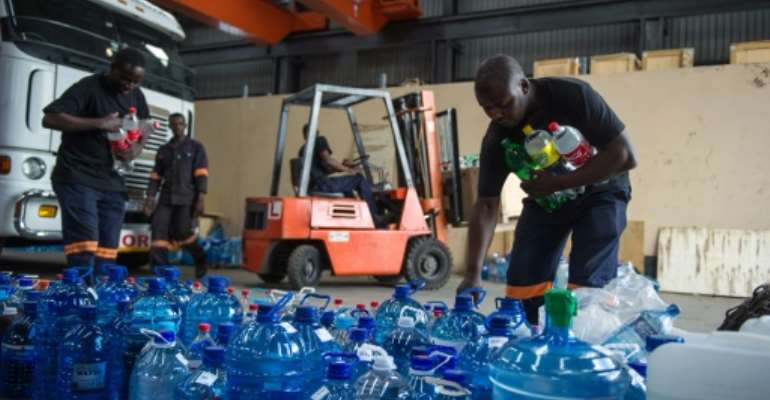 Factory workers in Benoni on the outskirts of Johannesburg, South Africa pile up donated water bottles by residents to be delivered in drought stricken rural communities on January 15, 2016.  By Mujahid Safodien (AFP/File)