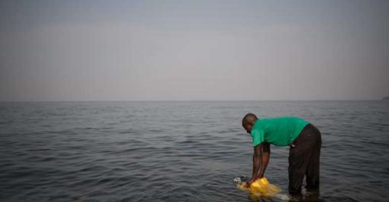 A man fills a jerrycan with water from Lake Kivu on the Himbi beach in Goma, in the east of the Democratic Republic of Congo on August 11, 2013.  By Phil Moore (AFP/File)
