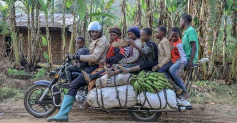 What, no kitchen sink? A giant motorbike in Cameroon takes a driver, six passengers and plenty of luggage.  By Daniel Beloumou Olomo (AFP)