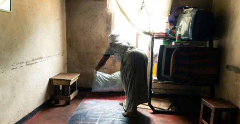 Where a child is born: Esther Gwena, 69, who acts as a midwife but has no training, lays down sheets in her rundown apartment -- a makeshift maternity unit.  By Jekesai NJIKIZANA (AFP)