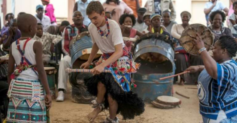 Kyle Todd (C) dances during his initiation ceremony to become a Sangoma at a traditional healer school in Pretoria, South Africa.  By Mujahid Safodien (AFP)