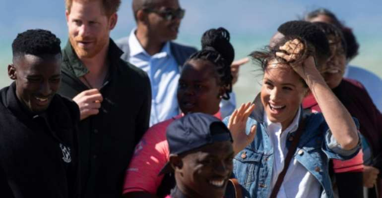 Wind and smiles: Prince Harry and his wife Meghan meet members of Waves for Change. The group uses surfing to help young people trapped in Cape Town's slums get a different perspective on life.  By DAVID HARRISON (AFP)