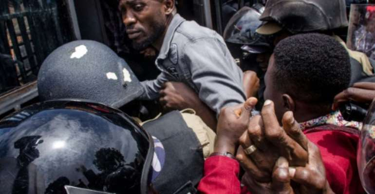 Wine (wearing a red beret) was dragged out of his car and arrested.  By Badru KATUMBA (AFP)