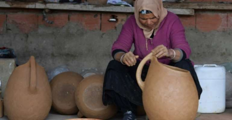 Women from Sejnane in northern Tunisia keep alive an ancient tradition of creating pottery with all-natural materials.  By FETHI BELAID (AFP)