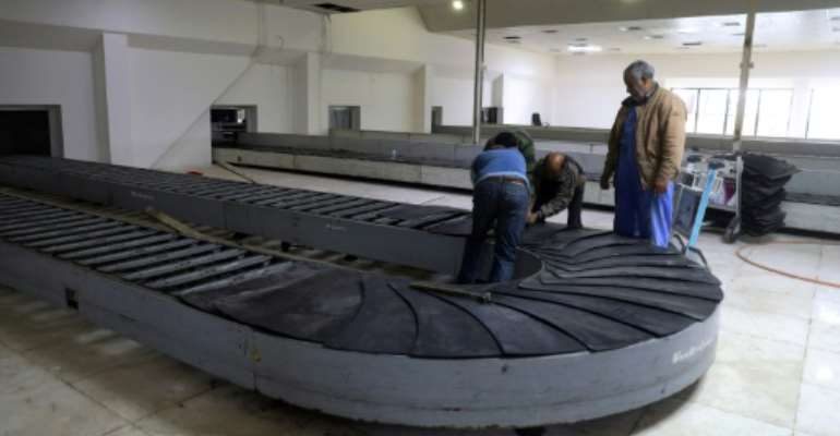 Workers at the Libyan capital's Mitiga airport.  By - (AFP)