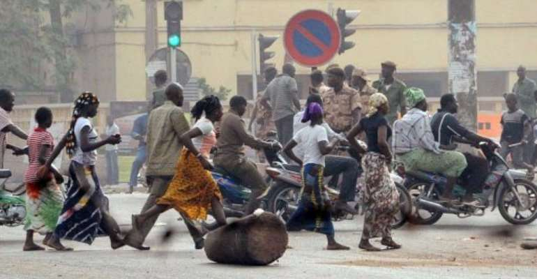Residents run past soldiers in a street of Bamako.  By Habibou Kouyate (AFP)
