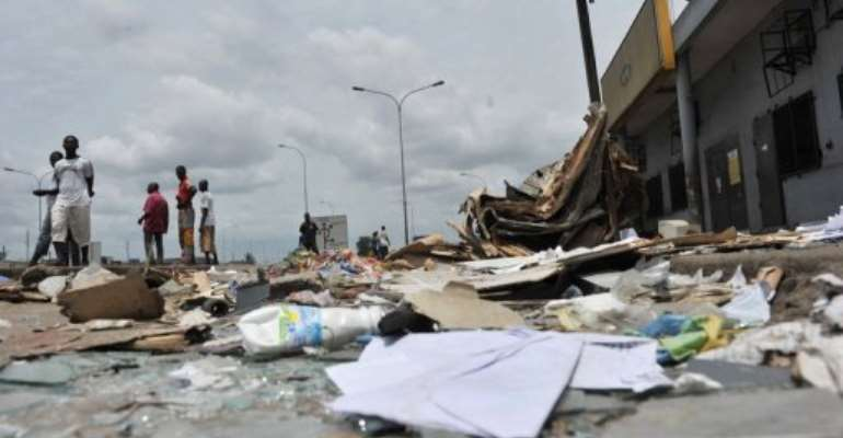 Resident walk past shops looted and destroyed in the Abobo district of Abidjan in 2011.  By Issouf Sanogo (AFP/File)