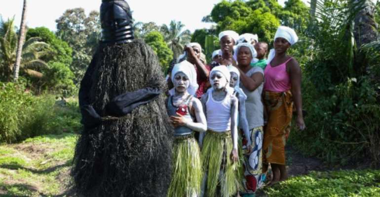 Young girls in white face paint take part in a procession to start their initiation into the Bondo secret society, alongside a figure called the Black Devil.  By LYNN ROSSI (AFP)