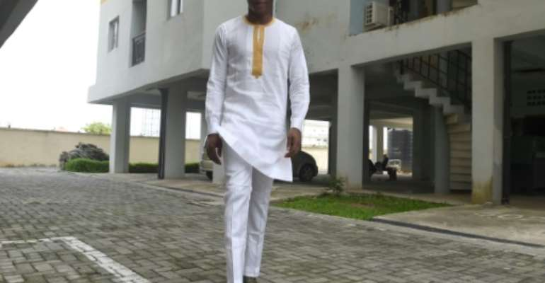 Young Nigerian men are turning from desiger jeans to traditional dress, like this white bua and sokoto style, starting a new fashtion trend.  By PIUS UTOMI EKPEI (AFP)