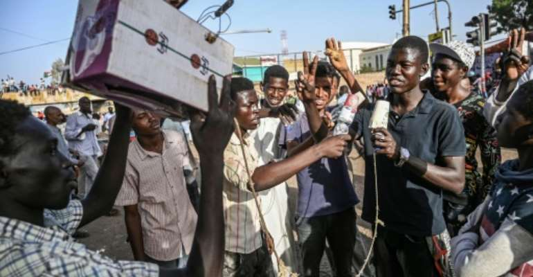 Young Sudanese protesters mimic journalists -- complete with a cardboard mocked up camera and a plastic bottle to represent a microphone -- to poke fun at state TV for failing to cover demonstrations.  By OZAN KOSE (AFP/File)