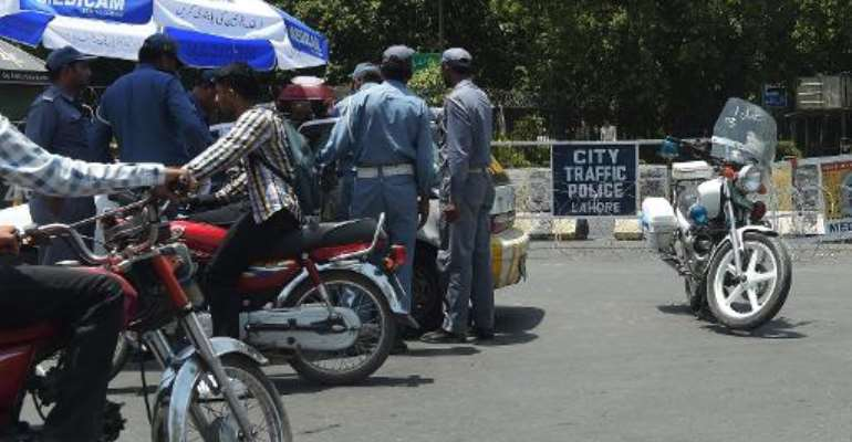 Traffic police gather at the end of a cordoned-off street leading to the hotel where the Zimbabwe and Pakistani cricket teams are staying in Lahore, northeast Pakistan on May 30, 2015.  By Aamir Qureshi (AFP)