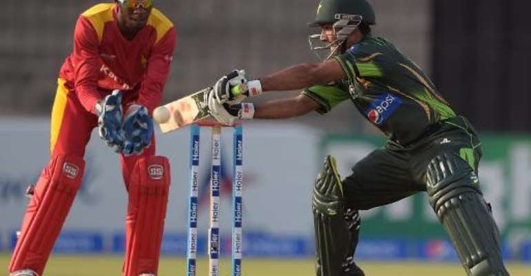 Pakistan's Asad Shafiq (right) plays a shot as Zimbabwe's wicketkeeper Richmond Mutumbami looks on during their third and final one day international match at the Gaddafi Stadium in Lahore on May 31, 2015.  By Aamir Qureshi (AFP/File)