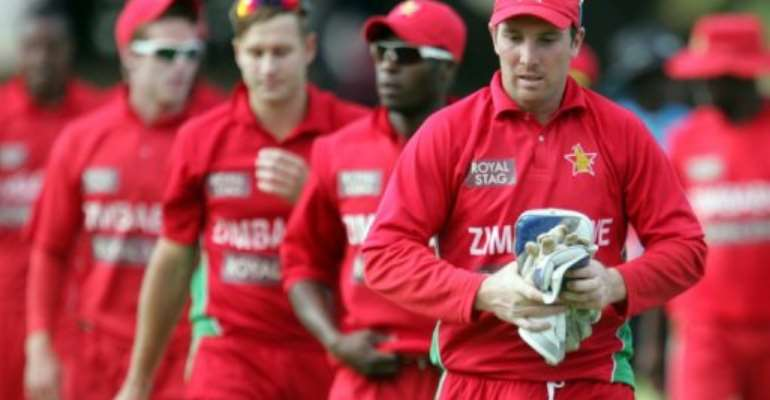 Zimbabwe's Brendan Taylor leaves the field with teammates after loosing to India, in Harare, on August 3, 2013.  By Jekesai Njikizana (AFP/File)