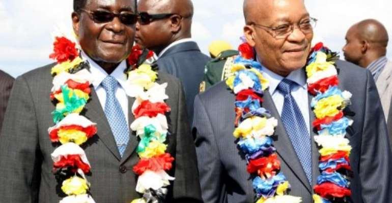 Robert Mugabe (left) with Jacob Zuma at Harare International airport in 2010.  By Jekesai Njikizana (AFP)