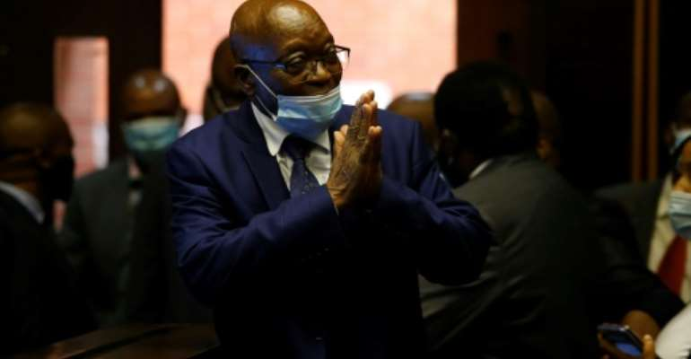 Zuma greets supporters before his corruption trial is postponed.  By ROGAN WARD (POOL/AFP)