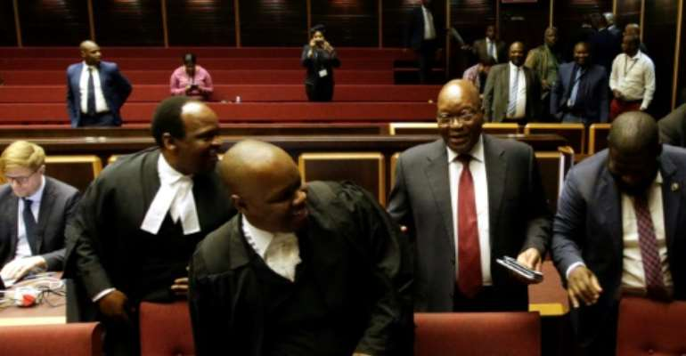 Zuma (second R) told supporters outside the court he has had to sell hats and socks to pay legal fees.  By Themba Hadebe (POOL/AFP)