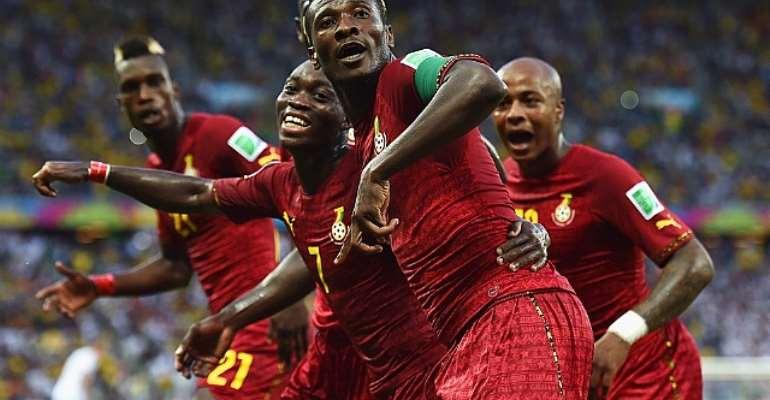 Asamoah Gyan of Ghana celebrates scoring with his teammates
