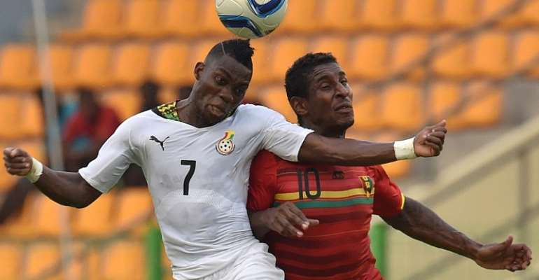Ghana's Christian Atsu (L) vies with Guinea's Kevin Constant (R)
