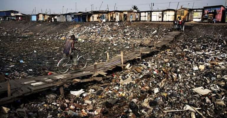 At the edge of the Agbogbloshie dump, a man cycles across a stretch of what was once part of the Korle Lagoon