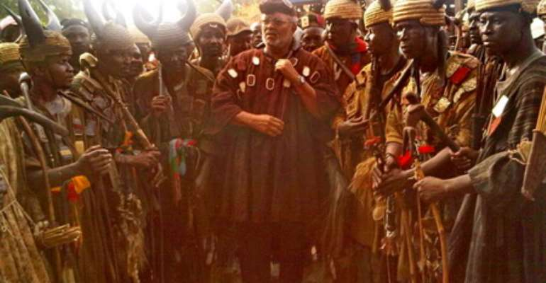 Ex-President Rawlings in traditional battle garb as he poses with the warriors