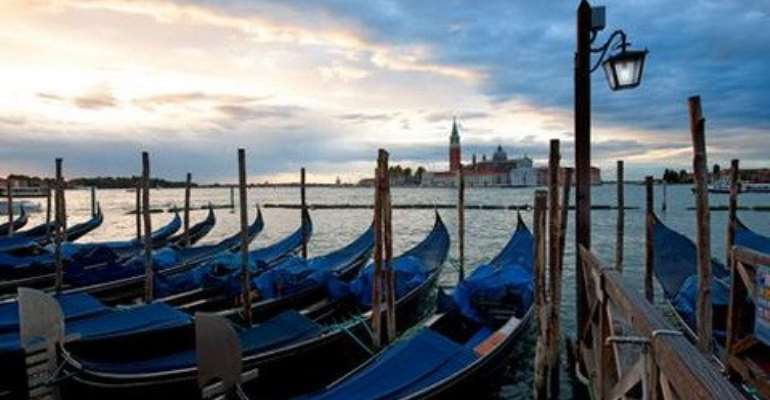 The gondolas bob on the water as the sun sets over Venice. (Pete Seaward)