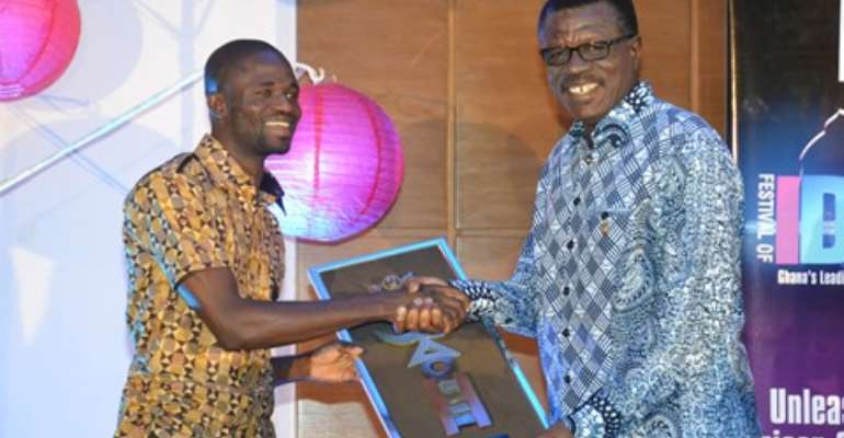 Manesseh Azure Awuni (left) being presented with an award by Dr. Mensa Otabil