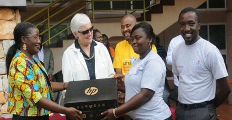 Second Lady Mrs. Amissah-Arthur (left) presenting an HP Lap Top to the overall best participant, Ayesu Belinda of Boso Anglican Primar