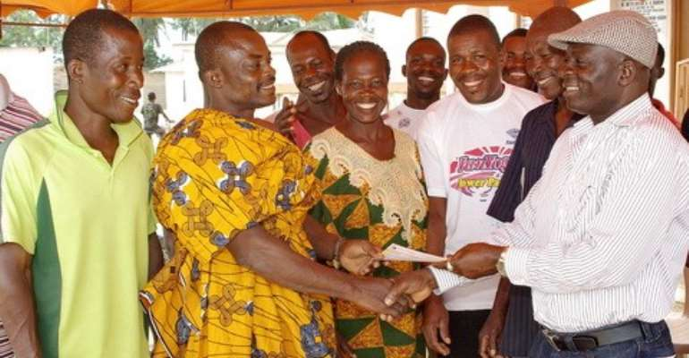 Hon. Kuntu Blankson, (right) presenting the cheque to Nana Kweku Badu, Ag regent of the village and his people.