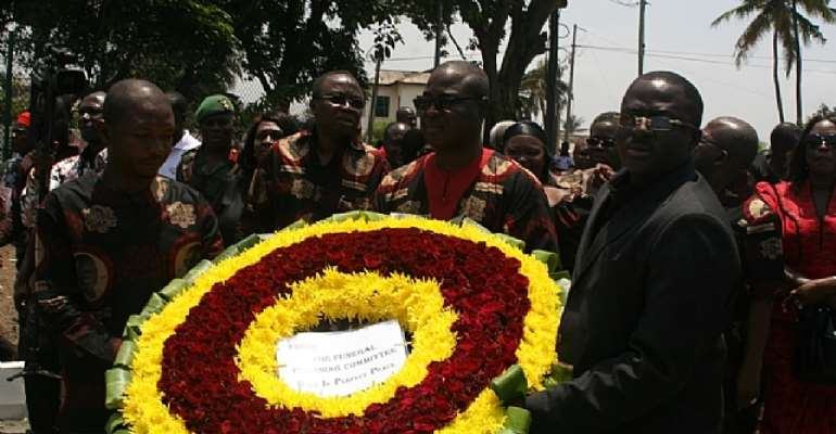 Members of funeral planning committee pay respects to the late President Mills