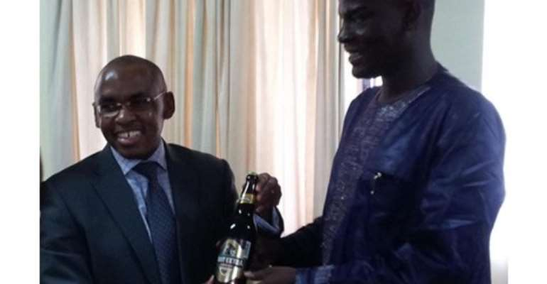 Mr. Peter Ndegwa (l) MD of GGBL presenting the Ruut Beer to Haruna Iddrisu, Minister of Trade.