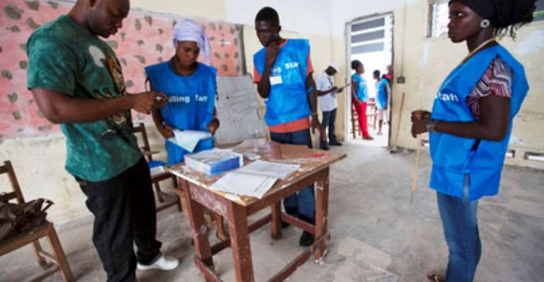 UN Photo/Staton Winter Liberian polling staff prepare ballots before inviting citizens into a polling station to vote in their country's constitutional referendum, in Monrovia.