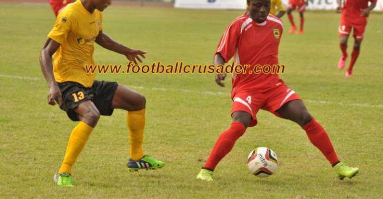 Kwame Boateng tries to beat AshantiGold's Desmond Agbekpornu.