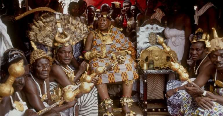 The late Asante King of Ghana; Otumfuo Opoku Ware II seated fourth from left in photo with his subjects and adorned in Ashanti Kente cloth and gold, to his right is the legendary Golden stool.