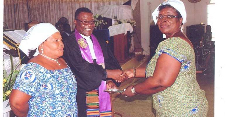 Rev. Enoch Adjei Pobee (standing) inducting Rev. Mark Boye. Left is his wife, Regina