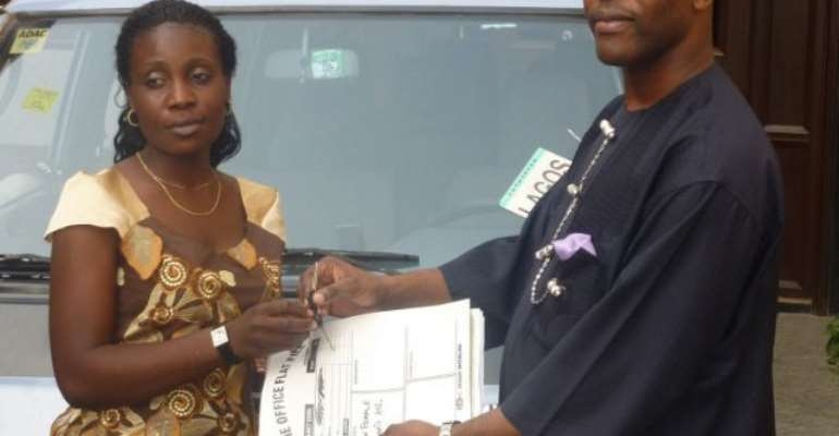 The Prince handing over the key and particulars of the bus to Mary, president of the Ijaw Female Students Association