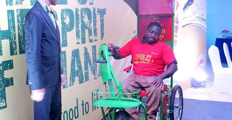 CEO of Avnash Industries Ghana Limited, Mr. Jai Mirchandani, Looks On As One of Disabled Persons Demonstrate The Use Of The Tricycle