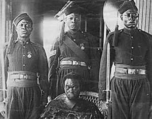Oba Ovonramwen, during whose reign the British looted the Benin Bronzes with guards on board ship on his way to exile in Calabar in 1897. The gown he is wearing hides his shackles. Photograph by the Ibani Ijo photographer J. A. Green. From the Howie photo album in the archives of the Merseyside Maritime Museum