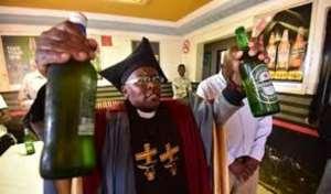 Pastor Tsietsi prays on the beer before serving