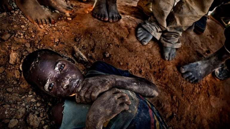 A young boy lies exhausted on the ground in a gold mine in Burkina Faso
