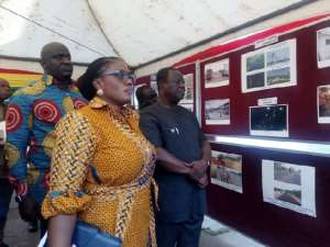 Kwasi Amoako-Atta (left), Deputy Minister of Roads, Anthony Karbo (right) and Deputy Minister of Information, Ama Dokuaa Asiamah Agyei, observing photos of some ongoing and completed roads and bridge projects shortly before the press conference