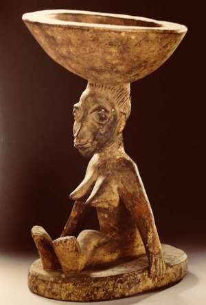 Ifa bowl, agere ifa, carried by a seated woman, Yoruba, Nigeria, now in Ethnologisches Museum, Berlin, Germany.<