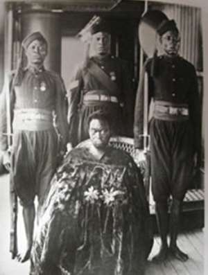 Oba Ovonramwen, during whose reign the British looted the Benin Bronzes, with guards on board a ship on his way to exile in Calabar in 1897. The gown he is wearing hides his shackles. Photograph by the Ibani Ijo photographer J. A. Green. From the Howie photo album in the archives of the Merseyside Maritime Museum.