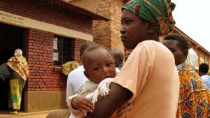 A mother and her child wait at an HIV clinic