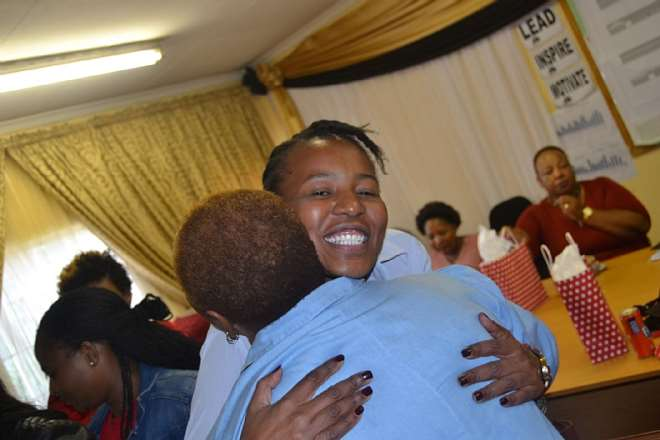 0170: Former Ntsikana Primary School graduate, Ms Sisanda Mamanzi, who now works for Bureau Veritas, greets an educator before signing the Visitor's Book at the Ithemba Trust International Women's Day 2019 celebration held in Daveyton, South Africa recently.