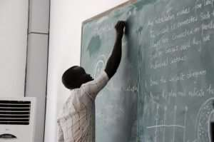 Teacher Shoulder Printing Of Exam Papers For Pupils In Tamale