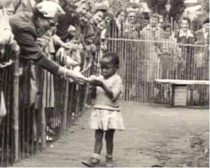 An African child in a Belgium zoo being fed with banana