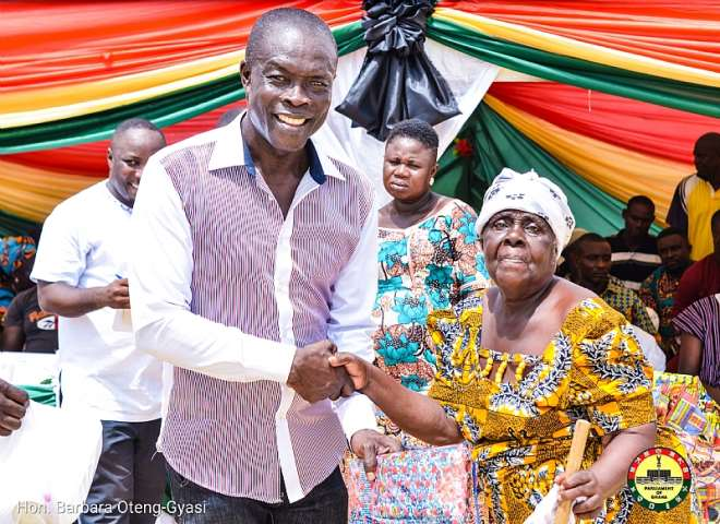 Constituency Chairman, Mr. Abbeam Danso presenting a cloth to a widow