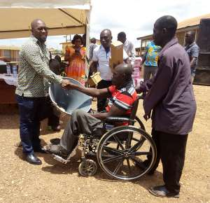 Hon. Mozart presenting Horns to a beneficiary